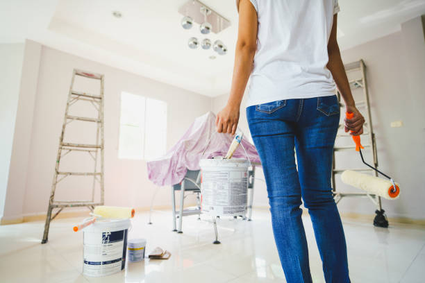 Jeune femme qui tient un pot de peinture pour rénover sa maison