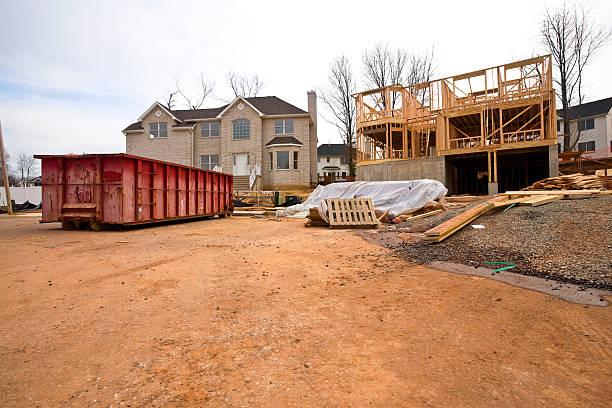 Préparation du chantier de rénovation d'une maison avec l'installation d'une benne pour les déchets