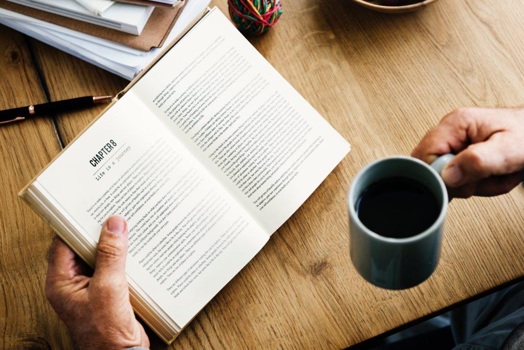 Une personne en train de lire un livre et boire un café sur une table en bois