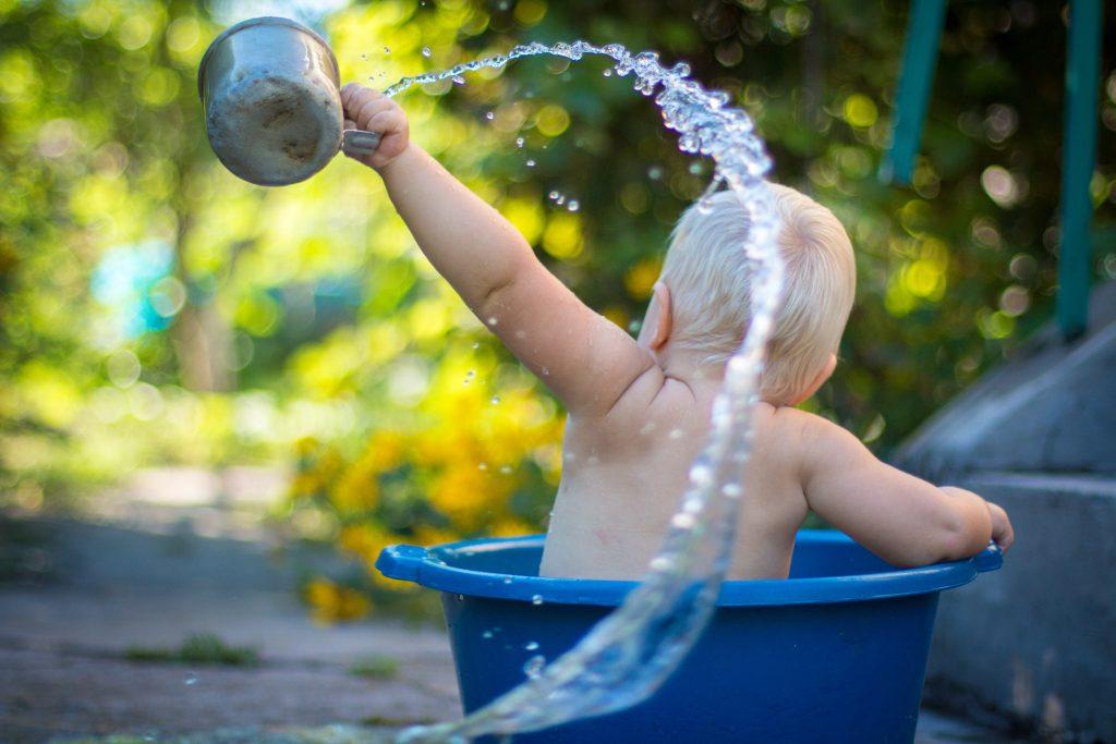 Enfant jouant dehors dans un bac d'eau