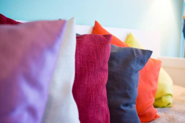 Plusieurs coussins de couleurs sur un lit