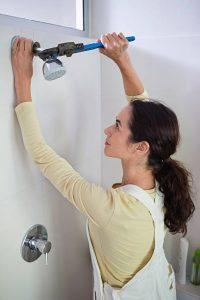 Femme en train d'installer une douche dans sa salle de bain
