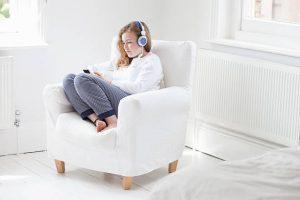 Femme assise dans un fauteuil blanc avec un chauffage électrique derrière elle
