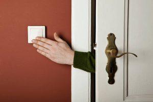 Main passant par l'ouverture d'une porte pour allumer un interrupteur