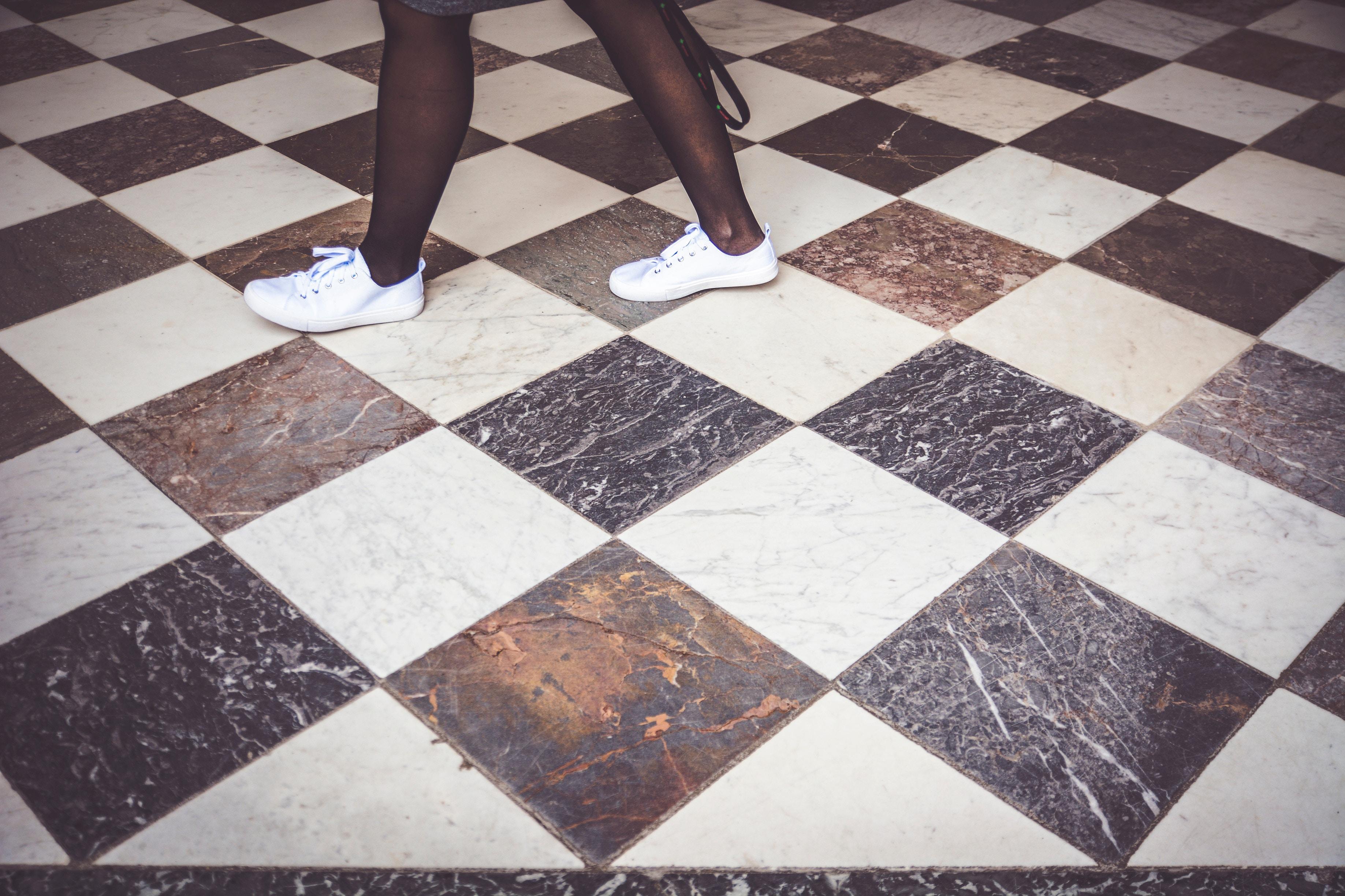 Jambes d'une jeune fille en train de marcher sur du carrelage noir et blanc