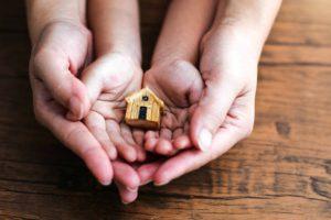 Parent tenant les mains de son enfant dans les siennes et une maison en bois en jouet