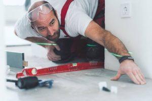 Ouvrier en train de vérifier le niveau du sol pour carreler