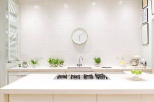 Cuisine blanche et propre avec horloge et plantes autour de l'évier