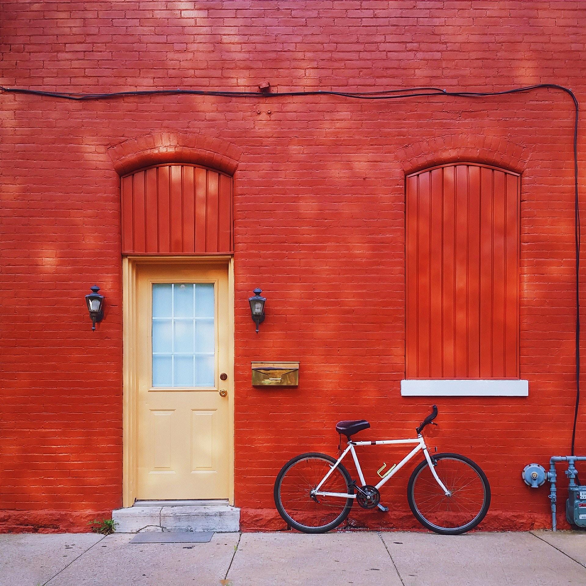 Porte d'entrée rue maison rouge avec vélo posé devant