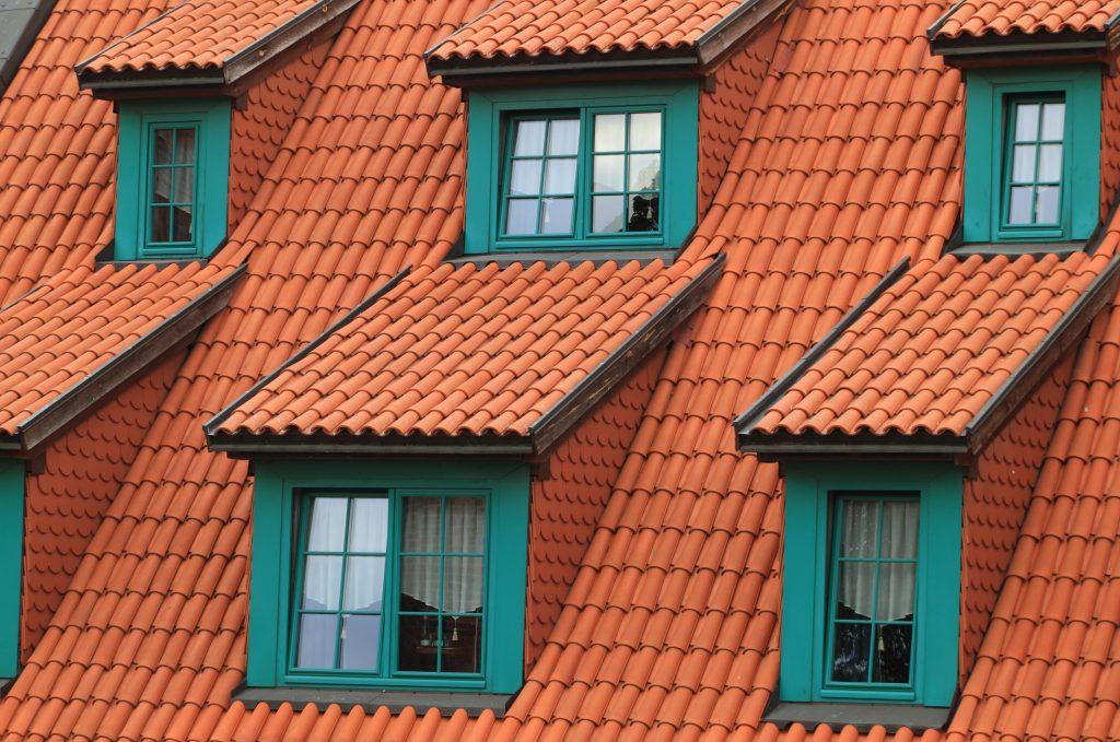Toit avec tuiles rouges et fenêtres vertes maison infiltration