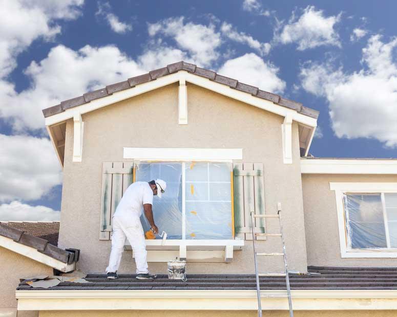 Façadier qui refait l'enduit d'une façade de maison