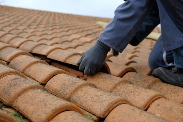 Couvreur en train de replacer une tuile sur un toit cassé