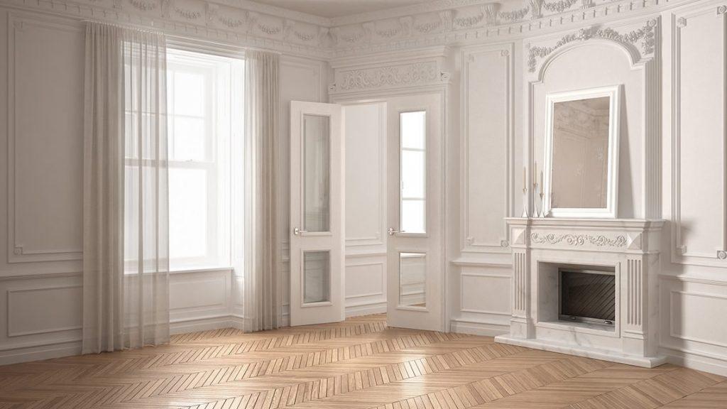 Appartement haussmannien avec un miroir moderne posé sur la cheminée