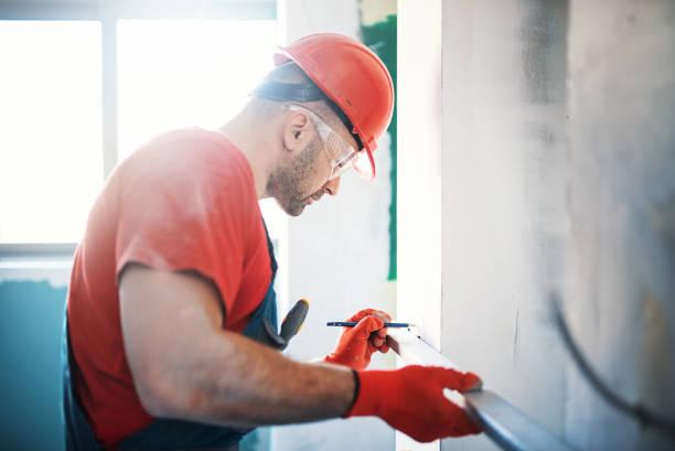 Ouvrier qui prend les mesures d'un mur en travaux
