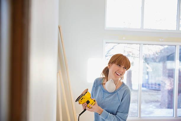 Femme qui ponce un mur avec une ponceuse angulaire